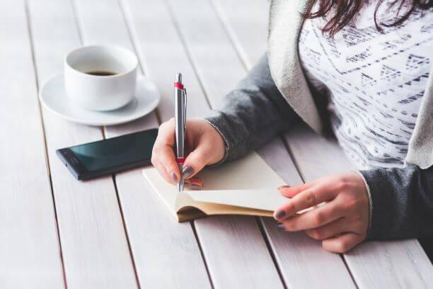 kobieta pisząca w notesie